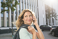 Portrait of confident woman on cell phone in the city - PNEF00100