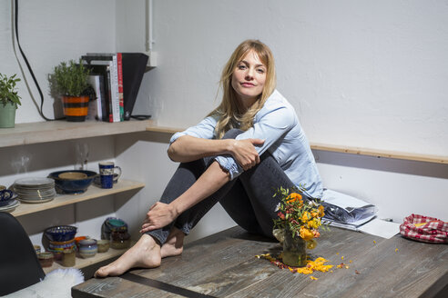 Blond woman at home sitting on wooden table - PNEF00106