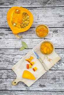 Two glasses of sweet-and-sour pickled pumpkin and ingredients on wood - LVF06320