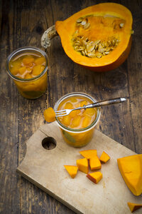 Glasses of sweet-and-sour pickled pumpkin and raw pumpkin on wood - LVF06326