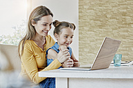 Happy mother with daughter at home looking at laptop - RORF01011