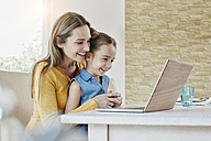 Happy mother with daughter at home looking at laptop - RORF01014