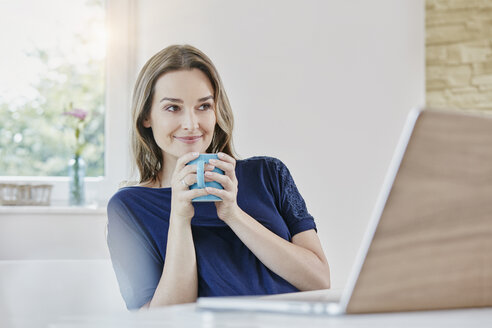 Smiling woman at home with coffee mug and laptop - RORF01017