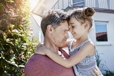Father holding daughter in front of their home - RORF01020