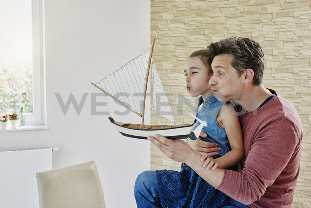 Happy father and daughter playing with model boat at home - RORF01035