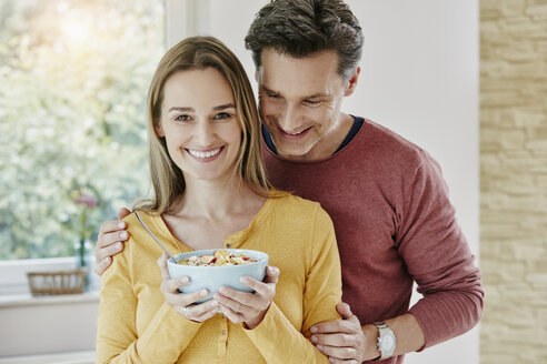 Happy couple holding bowl with muesli at home - RORF01038