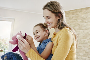 Happy mother and daughter playing with cuddly toy at home - RORF01041