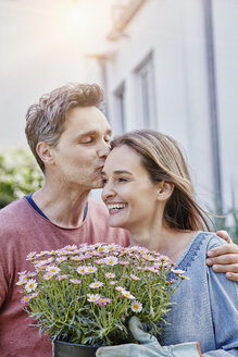 Man kissing wife with flowers in front of their home - RORF01050