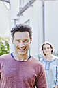 Portrait of smiling man with woman in background - RORF01053