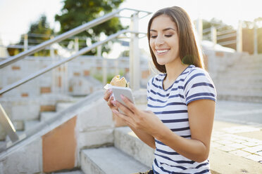 Young woman sitting on stairs eating bagel and using smartphone - BSZF00066