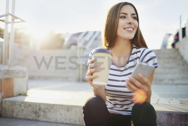 Young woman sitting on stairs in the city with phone and coffee - BSZF00069 - Bartek Szewczyk/Westend61