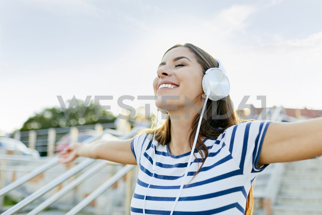 Happy young woman wearin headphones enjoying the summer - BSZF00072 - Bartek Szewczyk/Westend61