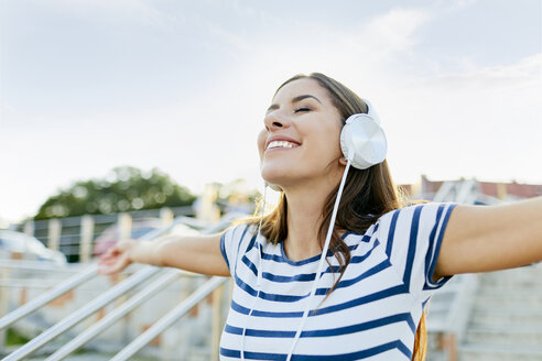 Happy young woman wearin headphones enjoying the summer - BSZF00072