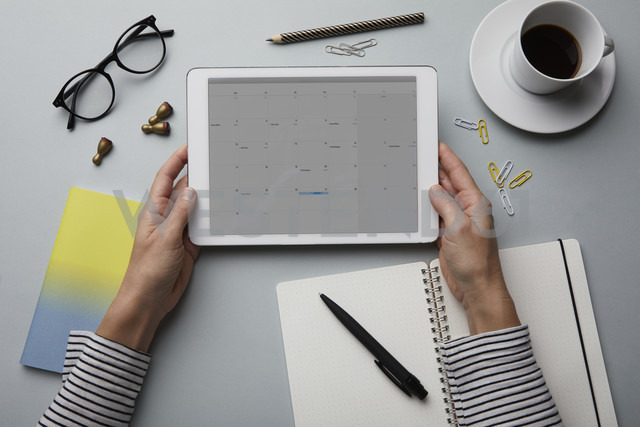Top view of woman holding tablet with calendar on desk - RBF06093 - Rainer Berg/Westend61