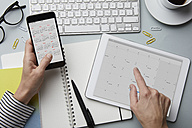 Top view of woman holding smartphone and tablet with calendar on desk - RBF06096