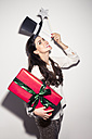 Happy young woman in party outfit holding large gift box - PNEF00110