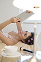 Happy young woman with curlers lying in bed using tablet - PNEF00116
