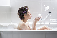 Young woman with curlers taking a bath - PNEF00119