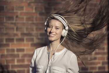 Portrait of happy woman with headphones and blowing hair - PNEF00123