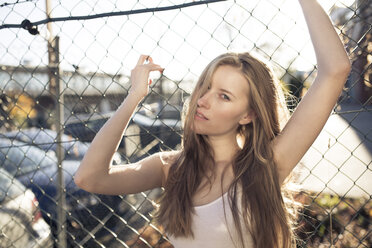 Portrait of young woman in front of wire mesh fence - PNEF00126