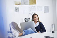 Smiling young woman using laptop at desk in office - PNEF00140