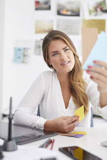 Young woman looking at notes at desk in office - PNEF00146