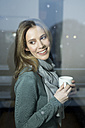 Smiling woman holding cup looking out of window - PNEF00149