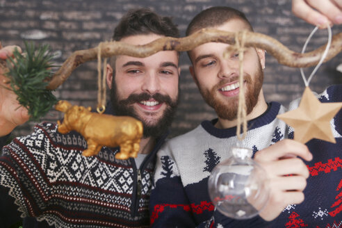 Gay couple decorating a branch at Christmas time - RTBF01034