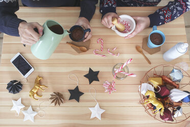 Gay couple preparing hot chocolate with cream and chopped candy canes at Christmas time, top view - RTBF01037