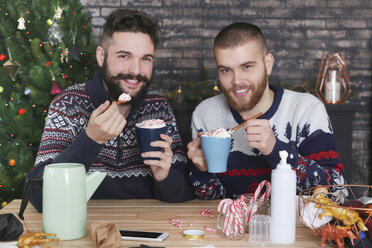 Happy gay couple drinking hot chocolate with cream and chopped candy canes at Christmas time - RTBF01040