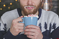 Man drinking hot chocolate with whipped cream and chopped candy canes at Christmas time - RTBF01043