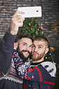 Portrait of happy gay couple taking selfie with smartphone at Christmas time at home - RTBF01052