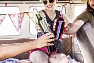 Happy friends inside van clinking bottles - FMKF04528