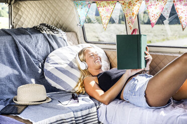 Happy woman with headphones lying in a van reading book - FMKF04534