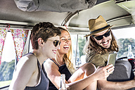 Happy friends inside van looking at smartphone - FMKF04537