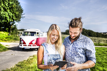 Happy couple outside van in rural landscape looking at tablet - FMKF04546