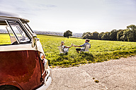 Couple on camping chairs clinking bottles next to van in rural landscape - FMKF04549