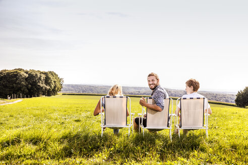 Friends sitting on camping chairs in rural landscape - FMKF04552