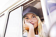 Young woman looking out of window of a van - FMKF04561