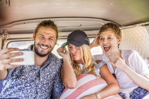 Happy friends inside van taking a selfie - FMKF04564