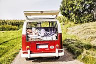 Woman lying in a van in rural landscape - FMKF04567