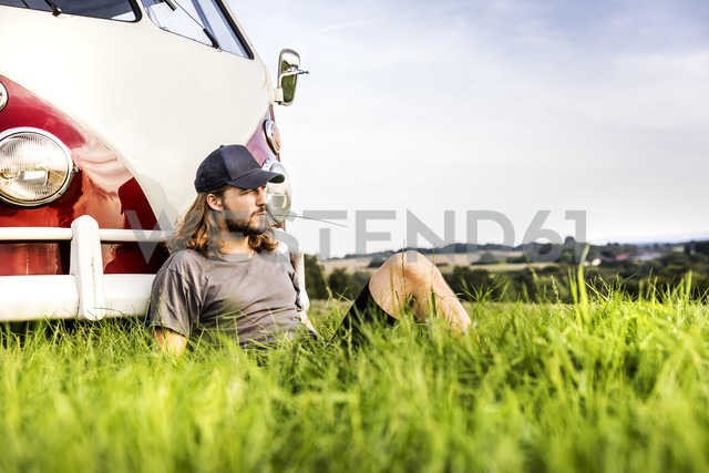 Young man sitting at a van on field in rural landscape - FMKF04576