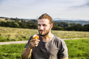 Young man eating an apple in rural landscape - FMKF04579
