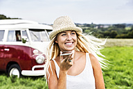 Happy young woman with cell phone in front of van in rural landscape - FMKF04588
