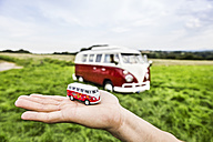 Woman's hand holding van model next to van in rural landscape - FMKF04591