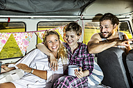 Happy friends inside a van enjoying coffee - FMKF04597