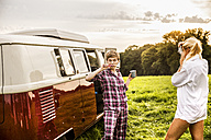 Woman taking picture of friend brushing teeth at a van in rural landscape - FMKF04600
