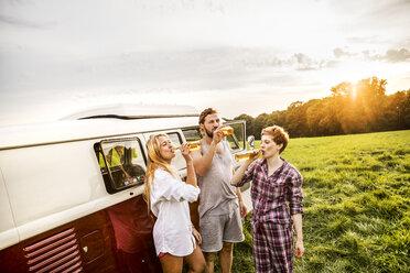 Friends in pyjamas drinking beer at a van in rural landscape - FMKF04603