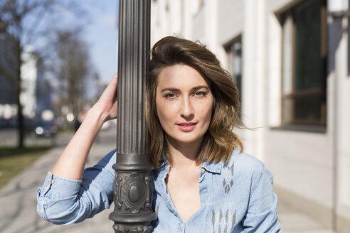 Portrait of woman leaning against lamp pole - PNEF00160