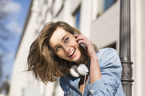 Portrait of laughing woman with headphones on the phone - PNEF00163